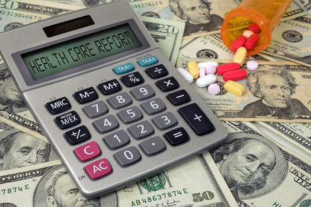 health care reform text on calculator and American money with variety of prescription drugs spilling out of orange pill bottle Stock Photo