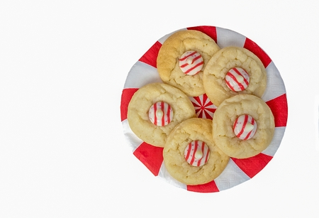 sugar cookies with red and white striped candy on round paper napkin isolated on white