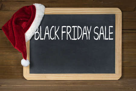 Red and white fur Santa hat on black chalkboard and rustic wood for Black Friday sale Stock Photo
