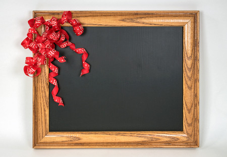red curly Christmas ribbon on retro black chalkboard with wooden frame