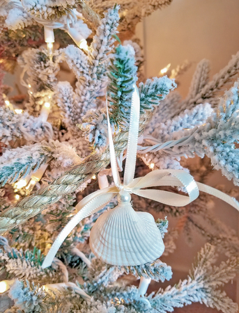 seashell Christmas ornament with pearl tied with white satin ribbon and rope garland on holiday tree Stock Photo