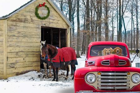 Camioneta pickup retro rojo y caballos por granero rural en invierno con corona de Navidad