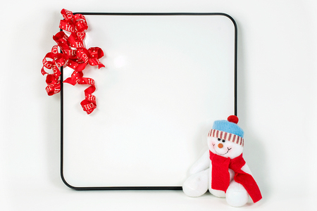 red Christmas ribbon on dry erase board with snowman on white background Stock Photo
