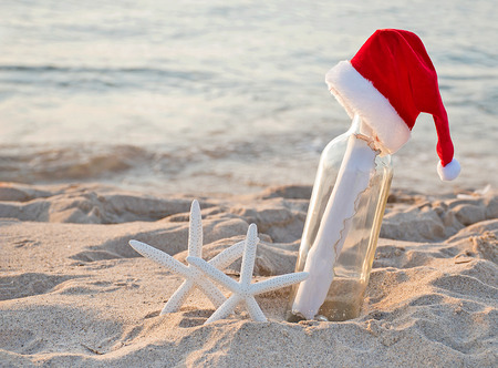 Santa hat on message in a bottle with white starfish in beach sand