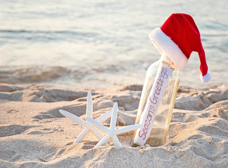 Santa hat on message in a bottle with white starfish in beach sand and Seasons Greetings sign
