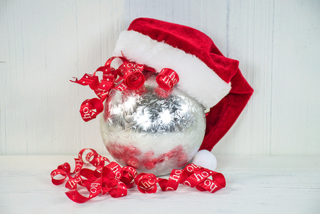 silver Christmas ornament with Santa hat and curly red ribbon on whitewashed wood Stock Photo