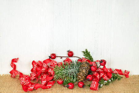 Christmas ribbon with red berries and pine cone bouquet on brown burlap