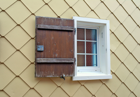 European house window with single rustic wooden shutter Stock Photo