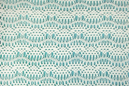 cream colored crochet lace pattern on pastel turquoise  background