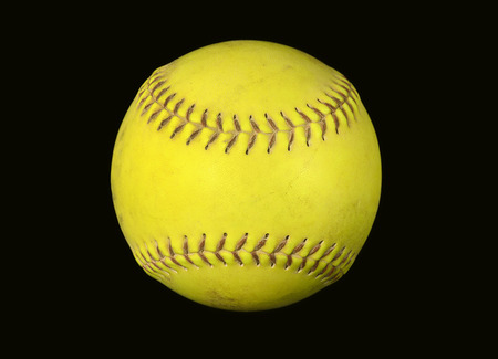 closeup of neon yellow softball isolated on black