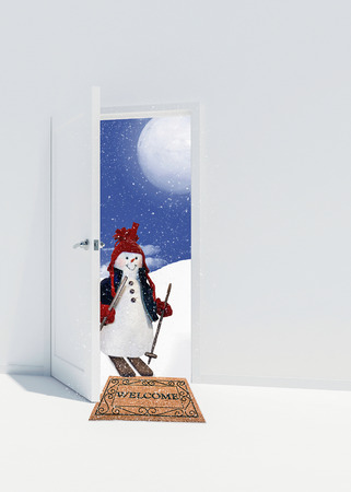 snowman on skis in open doorway with brown welcome mat and snowflakes