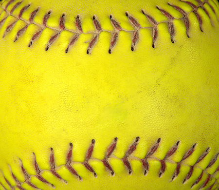 extreme close up of used neon yellow soft ball with red stitched seams