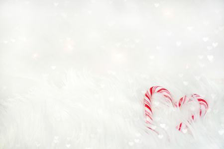 red and white striped Christmas candy cane heart in white fur with bokeh hearts
