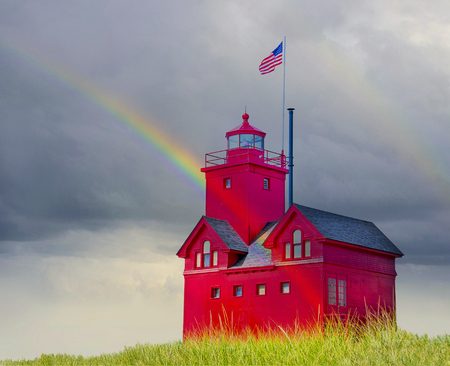 Michigan red lighthouse in dune grass with rainbow and storm clouds