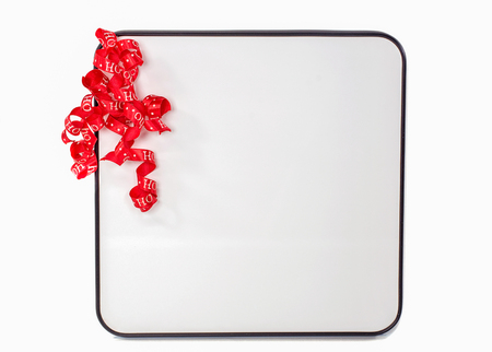 curly red Christmas ribbon on blank  white dry erase board isolated on white background