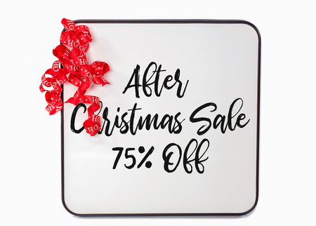 after Christmas sale sign with red curly ribbon on white dry erase board Stock Photo