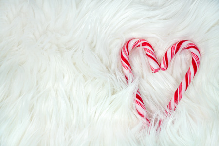 close up of red and white striped candy cane heart in white fur Stock Photo