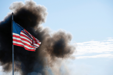 American flag illuminated by sunlight with cloud of black smoke Stock Photo