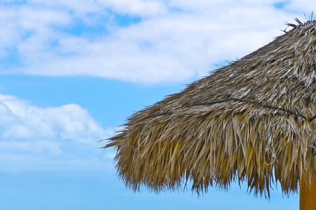 tropical thatched grass tiki hut roof with blue sky and clouds