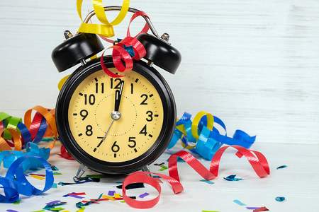 midnight time on retro black clock for New Years Eve party with colorful ribbon and confetti on whitewashed wood