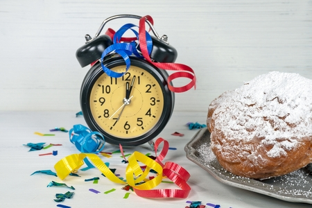 confetti and ribbon on retro clock with midnight time and New Years Dutch oliebollen on pewter plate Stock Photo