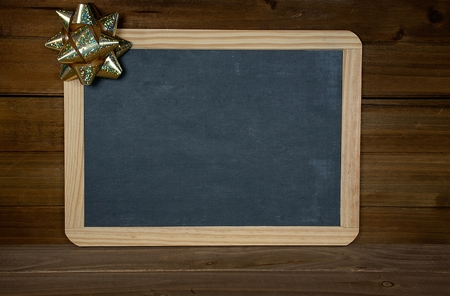 gold Christmas bow on blank black chalkboard on rustic wood