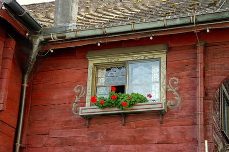Austrian house window with ornate design and red geranium plants in window box