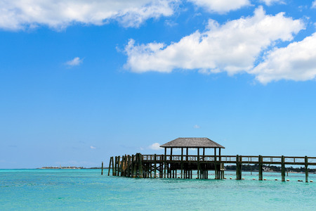 vacant rustic wooden pier in turquoise water color in Nassau Bahamas