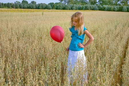 young Caucasian girl in Michigan wheat field with red balloon