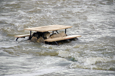 empty wooden picnic table on rocks in river flood