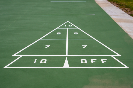 white and green painted shuffleboard game sign on pavement