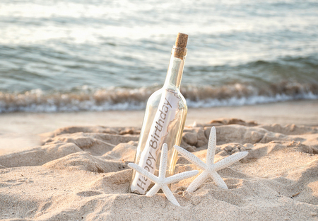 pair of white starfish with happy birthday message in a bottle on beach sand