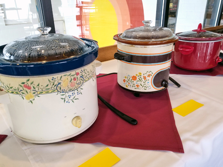 row of crock pots in restaurant chili cook off competition Stock Photo