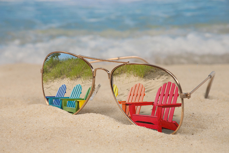 colorful row of Adirondack chairs reflected in aviator sunglasses in beach sand