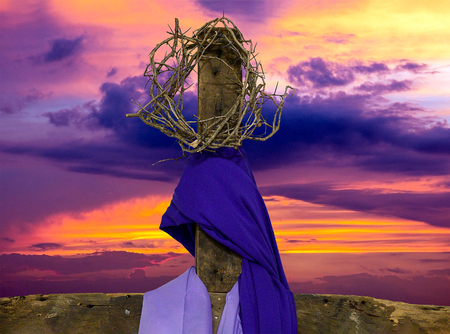 crown of thorns on rugged wooden cross with purple fabric drape and sunrise sky