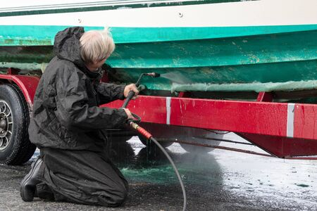 Caucasian man cleaning boat hull with pressure washer