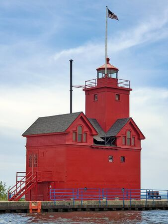 Bright red lighthouse on Holland Harbor pier with American flag in Holland Michigan