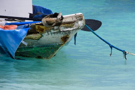 old fishing boat filled with junk moored by frayed rope in turquoise ocean water