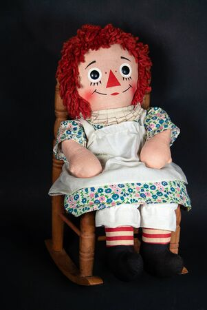old rag doll with white apron sitting on wooden rocking chair Stock Photo