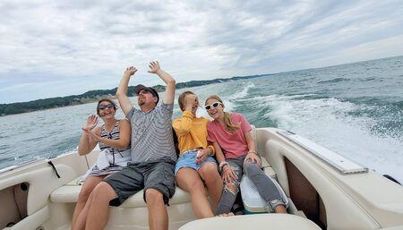 Caucasian family having fun riding in a power boat on Lake Michigan Фото со стока