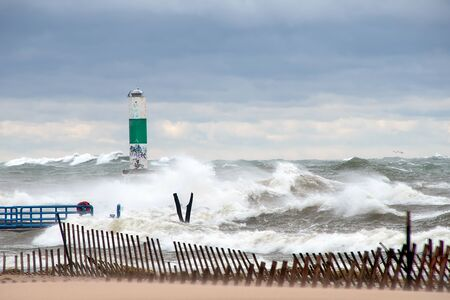 high waves on stormy Lake Michigan with green and white channel marker and beach fence Stockfoto - 132043830