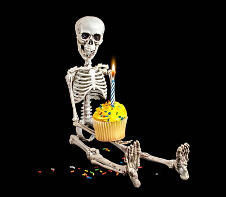 skeleton holding a birthday cupcake with yellow frosting and sprinkles isolated on black