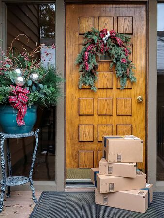 stack of brown cardboard boxes in front of wooden house door with Christmas decorations