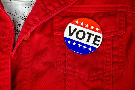 close up of political campaign vote button on red jacket pocket Stock Photo