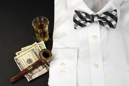 man's white dress shirt and black and white checkered bow tie with shot of whiskey and smoking pipe on American money
