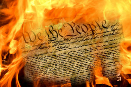 close up of United States constitution document burning in flames Stock Photo