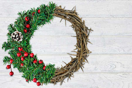 Christmas wreath and crown of thorns on rustic whitewashed wood background