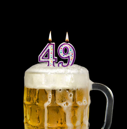 number 49 candle in beer mug for birthday celebration isolated on black