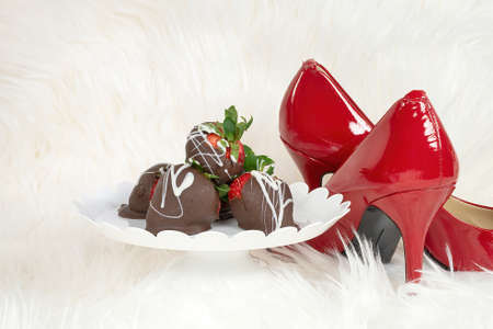 chocolate covered strawberries on pedestal dish on white fur with red pumps 版權商用圖片