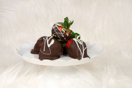 chocolate covered strawberries on white pedestal plate and fur